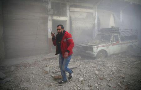 A Syrian Arab Red Crescent member walks at a site hit by airstrikes in the rebel held besieged Douma neighbourhood of Damascus, Syria February 19, 2017. REUTERS/Bassam Khabieh