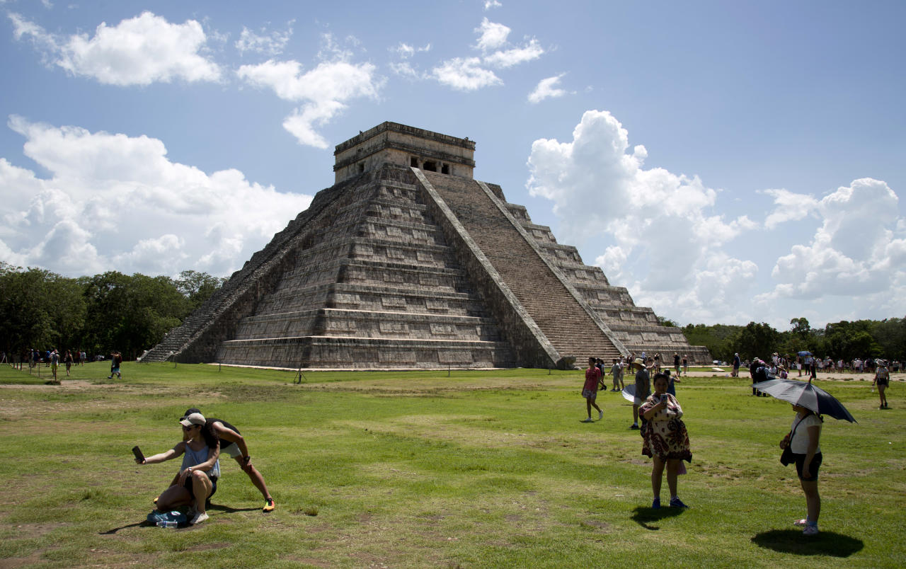 In this Aug. 3, 2018 photo, tourists walk at the Mayan ruins of Chichen Itza in Mexico's Yucatan Peninsula. Mexico's president-elect Andres Manuel Lopez Obrador wants to build a $3.2 billion train from the Yucatan Peninsula to Chiapas state to get tourists off the heavily travelled tourism route of Cancun-Riviera Maya-Chichen Itza-Xcaret visited by millions of tourists per year. (AP Photo/Eduardo Verdugo)