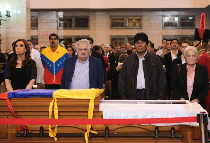 In this photo released by Miraflores Press Office, Argentina's President Cristina Fernandez, left, Venezuela's interim President Nicolas Maduro, second from left, Uruguay's President Jose Mujica, third from left, Bolivia's President Evo Morales, fourth from left, and Mujica's wife, Uruguayan Senator Lucía Topolansky stand next to the flag-draped coffin containing the body of Venezuela's late President Hugo Chavez on display during his wake in Fort Tiuna military academy where his body will lie in state in Caracas, Venezuela, Wednesday, March 6, 2013. Seven days of mourning were declared, all schools were suspended for the week and friendly heads of state were expected for an elaborate funeral Friday. (AP Photo/Miraflores Presidential Press Office)