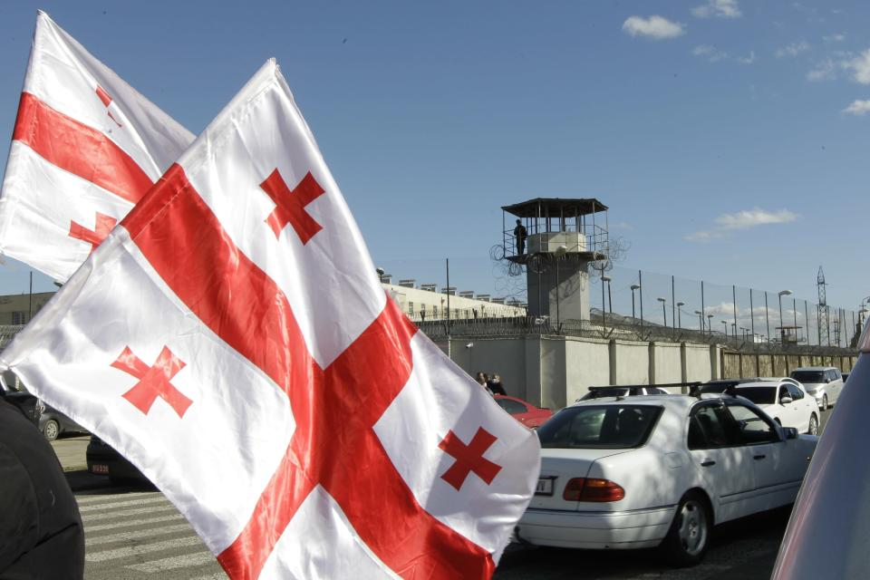 A soldier stands guard on a prison's watchtower as Georgian opposition supporters of former president Mikheil Saakashvili gather for a rally in his support in front of the prison where former president is being held, in Rustavi, about 20 km from the capital Tbilisi, Georgia, Monday, Oct. 4, 2021. Saakashvili was detained in Tbilisi on Saturday, Oct. 1, 2021. Georgia earlier declared Saakashvili wanted as a person convicted in absentia in several criminal cases and treated as a suspect in some others. Georgian authorities have warned repeatedly that he would be detained immediately once over the border. (AP Photo/Shakh Aivazov)