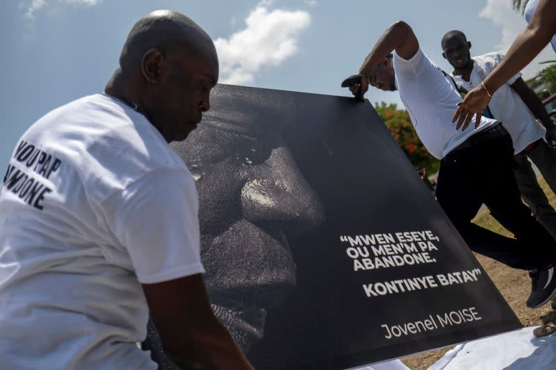 People place a portrait of late Haitian President Jovenel Moise at a memorial outside the Presidential Palace