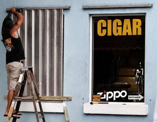 A man installs storm shutters, August 25, in Key West, Florida. Tropical Storm Isaac barreled toward Florida and was predicted to become a hurricane on Sunday, forcing a one-day delay to the Republican convention, after leaving two people dead in Haiti
