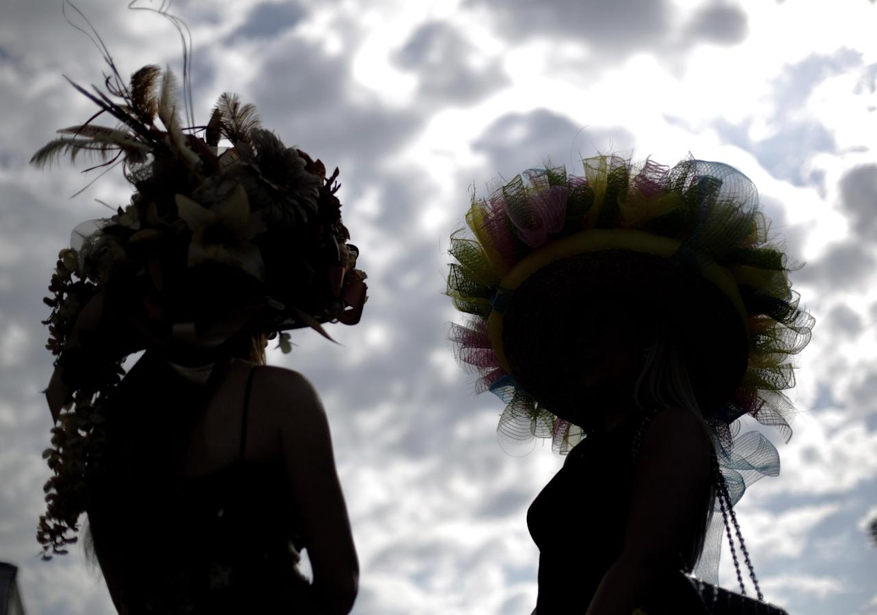 Ashley Cebak and Tami Purcell wear hats before the 140th running of the Kentucky Derby horse race at Churchill Downs Saturday, May 3, 2014, in Louisville, Ky. (AP Photo/David Goldman)