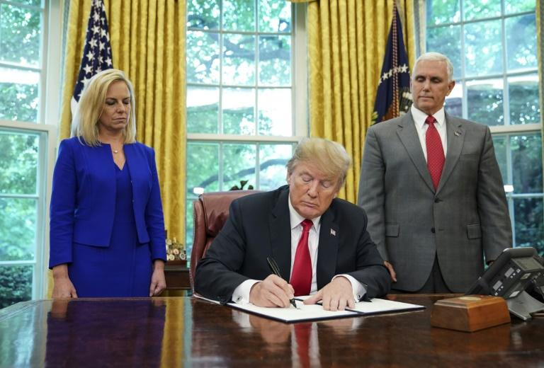 US President Donald Trump signs an executive order ending a policy of separating families caught crossing the US-Mexico border illegally