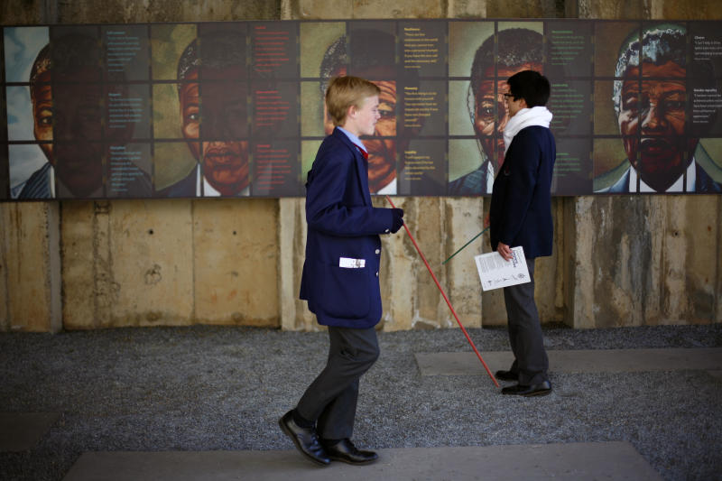South African pupils watch a temporary exhibit on Nelson Mandela at the Apartheid Museum in Johannesburg Tuesday June 11, 2013. Former South African President Nelson Mandela is spending a fourth day in a hospital, where he is being treated for a recurring lung infection. (AP Photo/Jerome Delay)