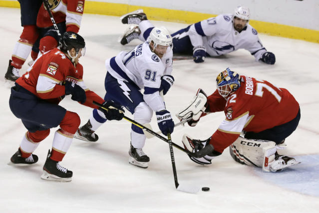 Tampa Bay Lightning's Steven Stamkos (91) scores a goal against Florida Panthers goalkeeper Sergei Bobrovsky, right, as Panthers' Dominic Toninato, left, defends during the first period of an NHL hockey game, Tuesday, Dec. 10, 2019, in Sunrise, Fla. (AP Photo/Luis M. Alvarez)