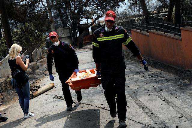<p>Firefighters carry a stretcher filled with body bags, following a wildfire at the village of Mati, near Athens, Greece, July 24, 2018. (Photo: Alkis Konstantinidis/Reuters) </p>