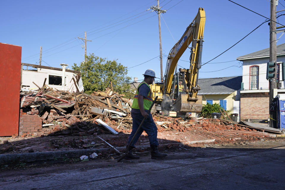 Workers remove debris from an unoccupied structure that collapsed yesterday as Hurricane Zeta passed through in New Orleans, Thursday, Oct. 29, 2020. The storm left much of the city and metro area without power. (AP Photo/Gerald Herbert)