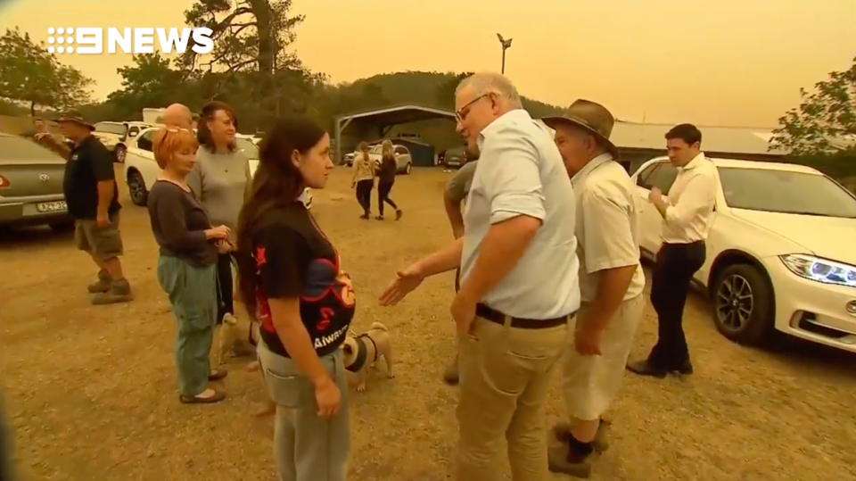 Prime Minister Scott Morrison offers a handshake to a woman in Cobargo.
