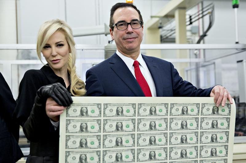 Treasury Secretary Steven Mnuchin and his wife, Louise Linton, pose on Wednesday holding a sheet of 50 $1 bills bearing Mnuchin's name.