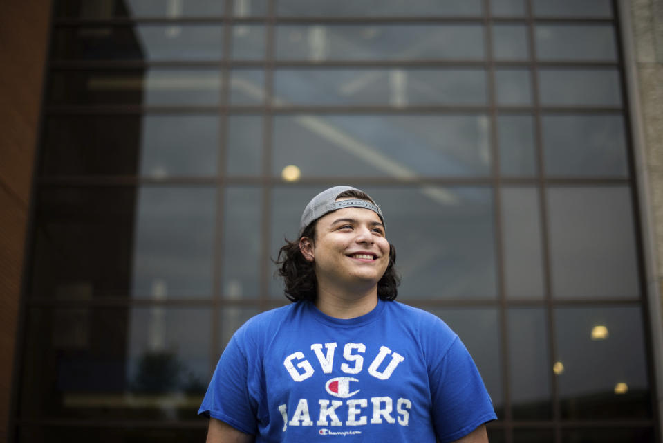 In this image provided by Grand Valley State University, Jordan Bernal, a Sport Management student at Grand Valley State University, poses outside Kindschi Hall of Science in Allendale, Mich. on Sept. 1, 2020. Bernal said first-generation college students like himself often struggle to find and take advantage of resources and scholarships once they enroll. (Kendra Stanley-Mills/ Grand Valley State University via AP)