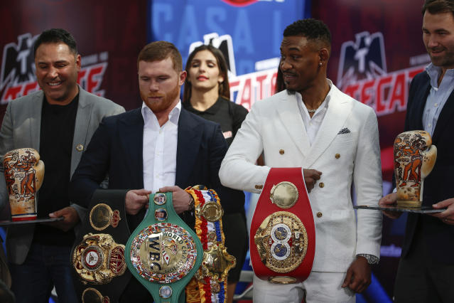 FILE - In this March 1, 2019, file photo, WBC and WBA middleweight world champion Canelo Alvarez, second from left, and IBF middleweight world champion Daniel Jacobs, second from right, pose with their title belts during a press conference in Mexico City. The moment won't be too big for Daniel Jacobs, of that he's certain. Not after going toe-to-toe with the fearsome Gennady Golovkin before dropping a narrow decision. Not after beating cancer that doctors were sure would end his career, if not his life. Canelo Alvarez will just be another obstacle in front of him when they meet Saturday night, May 4 in a middleweight title unification fight. (AP Photo/Anthony Vazquez, Fikle)