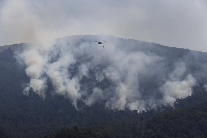 A Lebanese army helicopter flies over a forest fire on an extinguishing mission, at Qobayat village, in the northern Akkar province, Lebanon, Thursday, July 29, 2021. Lebanese firefighters are struggling for the second day to contain wildfires in the country's north that have spread across the border into Syria, civil defense officials in both countries said Thursday. (AP Photo/Hussein Malla)