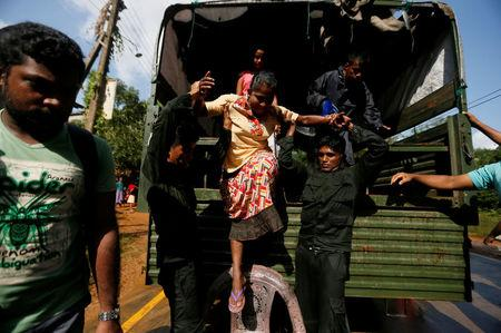 Sri Lankan army soldiers help a flood victim to get off from a truck during a rescue mission in Athwelthota village, in Kalutara, Sri Lanka May 28, 2017. REUTERS/Dinuka Liyanawatte