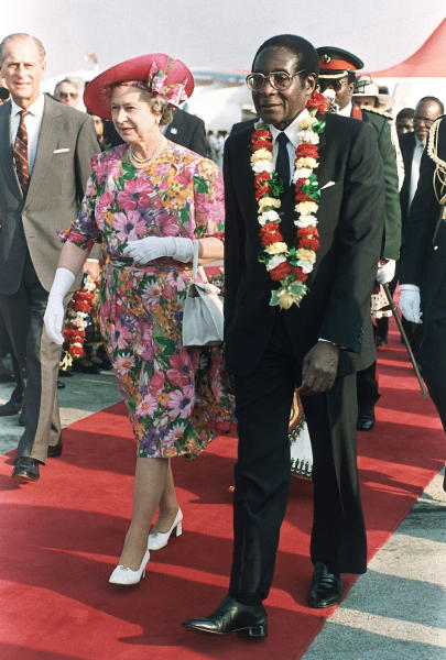 "FILE - In this file photo taken Oct. 10, 1991 Britain's Queen Elizabeth II is escorted by Zimbabwean President Robert Mugabe, right, after the Queen's arrival at Harare airport on a second visit to the country. Zimbabwe's longtime President Robert Mugabe says he doesn't want anyone to be fooled by his impeccable Western style of dress and his precise, teacherly use of English: He is African through and through. ""I am not British, I am not a colonial product because I am a complete Zimbabwean, "" he told graduates at Great Zimbabwe University near the remains of the 13th Century walled city, for which Zimbabwe, the former colony of Rhodesia, is named. (AP Photo/Gill Allen-file)"