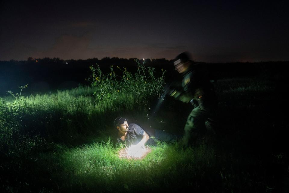 Border Patrol Agent Jesse Moreno, right, helps fellow agents detain three men suspected of illegally crossing into the USA in the wetlands along the U.S.-Mexican border near Granjeno, Texas, on July 13. The agents detained two men from Mexico and one from Honduras.