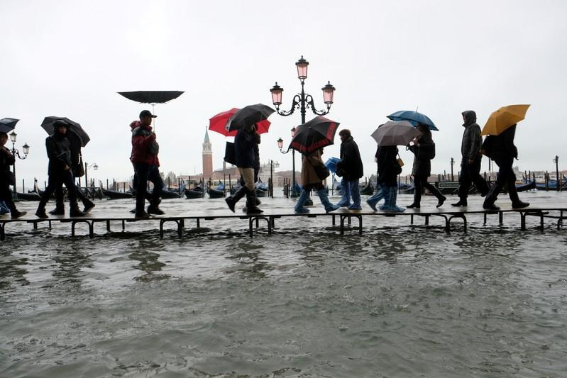 FILE PHOTO: People walk on a catwalk in the flooded St. Mark's Square in Venice, Italy