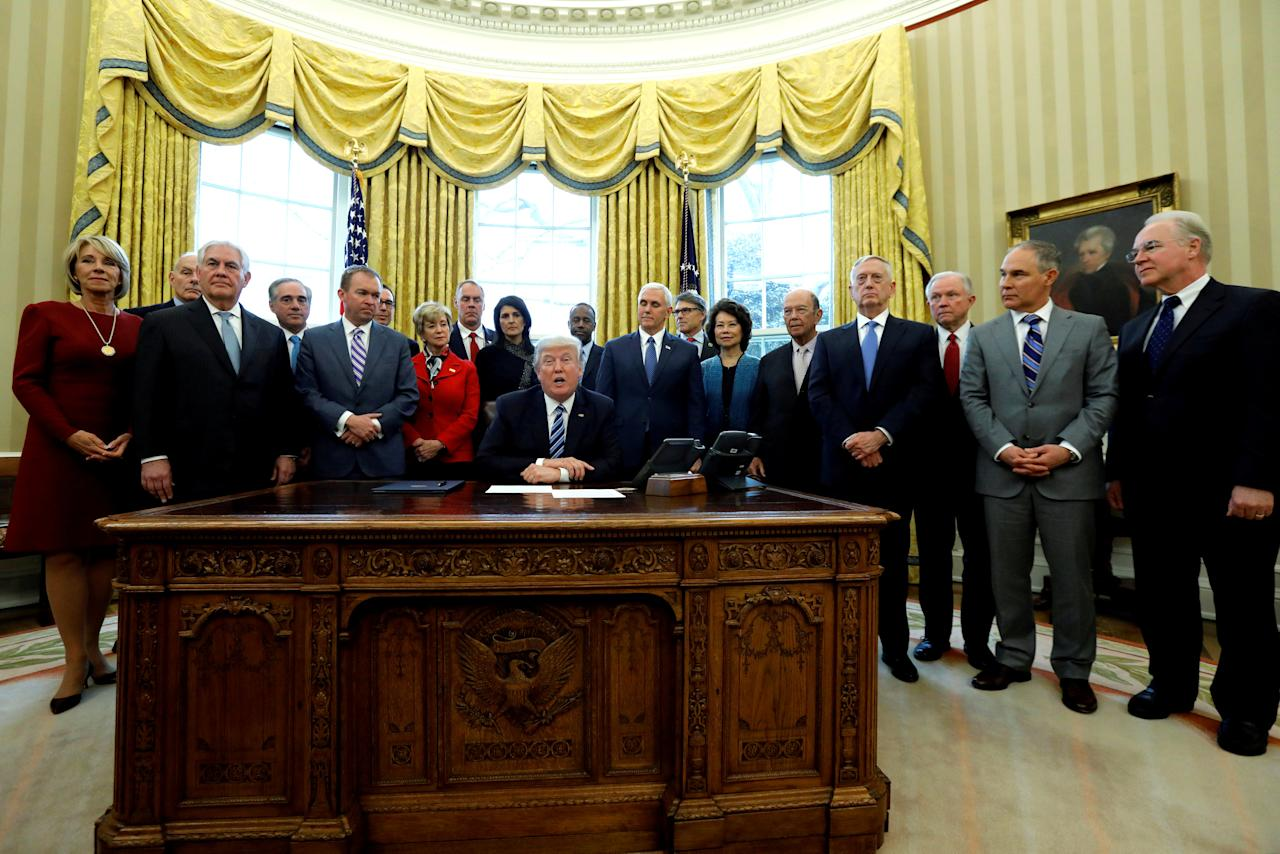 "U.S. President Donald Trump is surrounded by his cabinet, including Education Secretary Betsy DeVos (L-R), Secretary of Homeland Security John Kelly, Secretary of State Rex Tillerson, Secretary of Veterans Affairs David Shulkin, Office of Management and Budget (OMB) Director Mick Mulvaney, Treasury Secretary Steven Mnuchin, Small Business Administration (SBA) Administrator Linda McMahon, Interior Secretary Ryan Zinke, U.S. Ambassador to the United Nations Nikki Haley, Secretary of Housing and Urban Development (HUD) Ben Carson, Vice President Mike Pence, Energy Secretary Rick Perry, Transportation Secretary Elaine Chao, Commerce Secretary Wilbur Ross, Defense Secretary James Mattis, Attorney General Jeff Sessions, Attorney General Jeff Sessions, Environmental Protection Agency (EPA) Administrator Scott Pruitt and Secretary of Health and Human Services (HHS) Tom Price, as he signs an executive order entitled ""Comprehensive Plan for Reorganizing the Executive Branch"" in the Oval Office at the White House in Washington, U.S. March 13, 2017. REUTERS/Jonathan Ernst/File Photo"