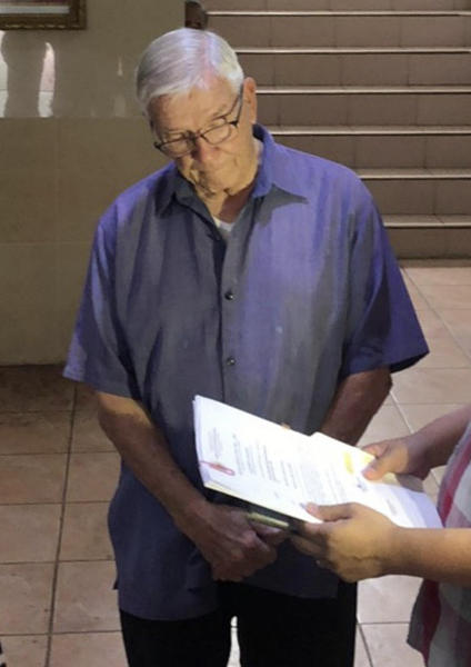 "In this Dec. 5, 2018, photo released by the Bureau of Immigration Public Information Office, American Roman Catholic priest Rev. Kenneth Bernard Hendricks looks at documents after being arrested in a church in Naval town in the island province of Biliran, central Philippines. Philippine immigration authorities say they have arrested Hendricks accused of sexually assaulting altar boys in a remote central town in a case one official described as ""shocking and appalling."" (Bureau of Immigration PIO via AP)"