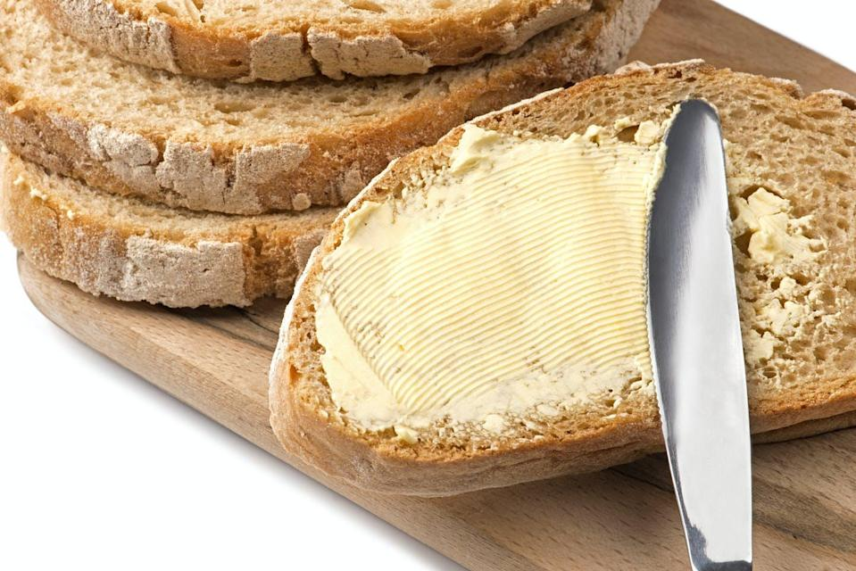 A knife spreading butter on bread