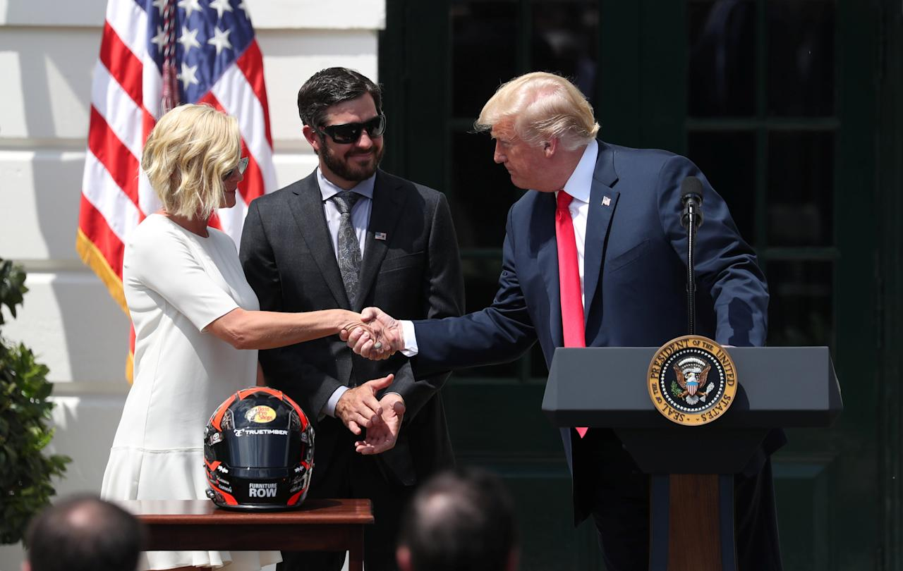 U.S. President Donald Trump shakes hands with Sherry Pollex as he welcomes her and her partner NASCAR Cup Series champion Martin Truex Jr. to the White House in Washington, May 21, 2018.   REUTERS/Kevin Lamarque