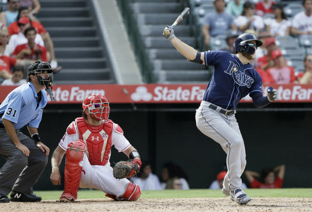 Tampa Bay Rays' Austin Meadows, right, follows through on his three-run home run, with Los Angeles Angels catcher Kevan Smith, center, and home plate umpire Pat Hoberg, left, watching, during the eighth inning of a baseball game in Anaheim, Calif., Sunday, Sept. 15, 2019. (AP Photo/Alex Gallardo)
