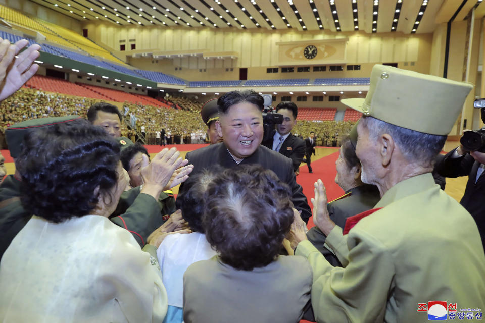 """In this photo provided by the North Korean government, North Korean leader Kim Jong Un, center, is welcomed by participants of a veteran conference in Pyongyang, North Korea, Thursday, July 29, 2021. North Korea said Friday, July 30, 2021 that Kim called for stronger capability to cope with any foreign provocation as he met with military officers ahead of annual drills next month between South Korea and the United States that Pyongyang views as an invasion rehearsal. Independent journalists were not given access to cover the event depicted in this image distributed by the North Korean government. The content of this image is as provided and cannot be independently verified. Korean language watermark on image as provided by source reads: """"KCNA"""" which is the abbreviation for Korean Central News Agency. (Korean Central News Agency/Korea News Service via AP)"""