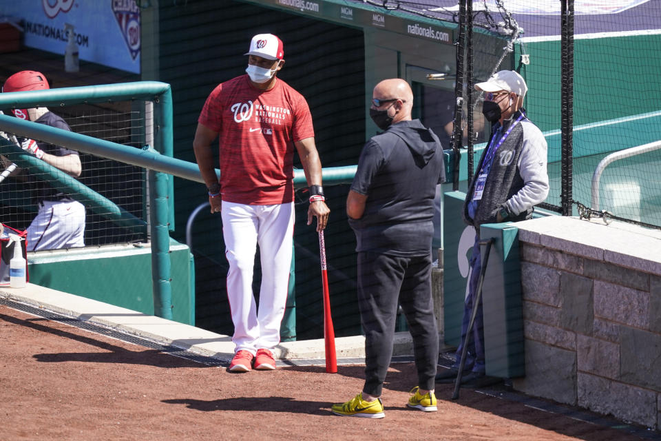Washington Nationals manager Dave Martinez, left, general manager Mike Rizzo, and owner Mark Lerner watch the team during a baseball workout at Nationals Park, Monday, April 5, 2021, in Washington. The Nationals are scheduled to play the Braves on Tuesday. (AP Photo/Alex Brandon)