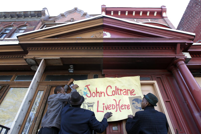 Men hang a banner on the former home, left, of jazz musician John Coltrane Friday, April 13, 2012, in Philadelphia. Jazz lovers and cultural officials in Philadelphia are promoting a fundraising effort to save the run-down house. Coltrane lived in a rowhouse in the city's Strawberry Mansion neighborhood from 1952 to 1958. (AP Photo/Matt Rourke)