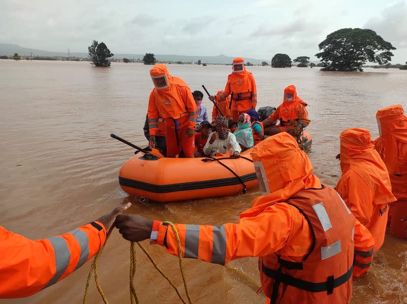 Members of NDRF evacuate people from a flooded area to safer places in Balinge village
