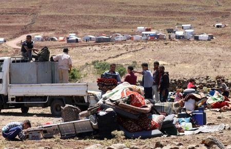 Internally displaced from Deraa province stand next to belongings near the Israeli-occupied Golan Heights, in Quneitra, Syria June 21, 2018. REUTERS/Alaa al-Faqir