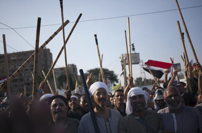 Supporters of Egypt's ousted President Mohammed Morsi hold up wooden sticks as they participate in a protest outside Rabaah al-Adawiya mosque, where protesters have installed a camp and held daily rallies at Nasr City, in Cairo, Egypt, Saturday, Aug. 10, 2013. Morsi supporters hunker down behind makeshift security barriers in preparation of a possible crackdown this week on their two main Cairo sit-ins. It comes as Egypt's leadership vows that the decision to disperse the sit-ins is irreversible. (AP Photo/Khalil Hamra)