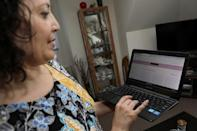 Lisa Batitto, demonstrates how she browses a clothing rental site at her home in Montclair, New Jersey