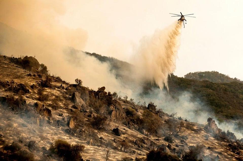 A helicopter drops water on the fire burning in Sequoia National Park in California (AP)