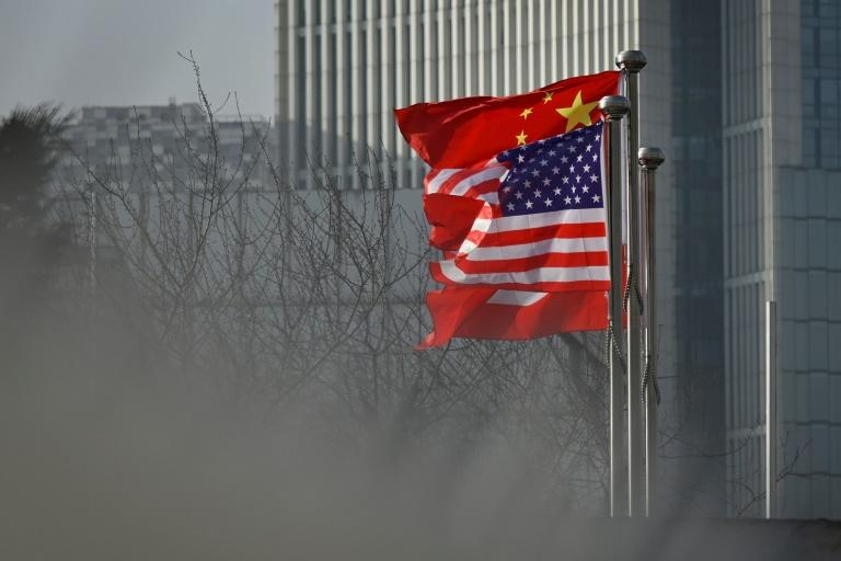 Chinese and US flags flutter outside a corporate building in Beijing in January 2020