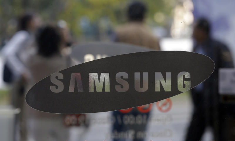 Visitors walk by the entrance to the Samsung Electronics Co. showroom at its headquarters in Seoul, South Korea, Friday, Oct. 26, 2012. Samsung's third-quarter net profit nearly doubled over a year earlier to a record high propelled by strong sales of Galaxy phones that helped widen its lead over rivals. (AP Photo/Lee Jin-man)