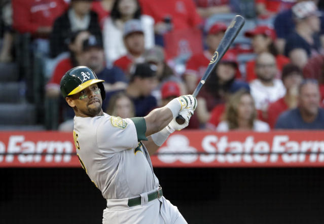 FILE - In this Sept. 29, 2018, file photo, Oakland Athletics' Khris Davis follows through on his two-run home run against the Los Angeles Angels during the first inning of a baseball game, in Anaheim, Calif. Davis led the majors in home runs, led the Oakland Athletics back to the playoffs for the first time in four years, then received a $6 million raise this offseason for a 2019 salary of $16.5 million. (AP Photo/Marcio Jose Sanchez, File)
