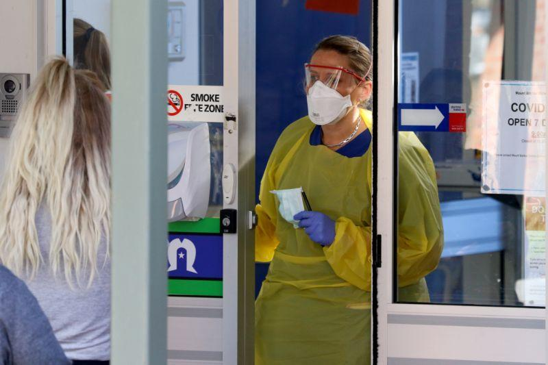 A nurse stands at a door with a mask on and speaks to patients at a coronavirus clinic in Adelaide.