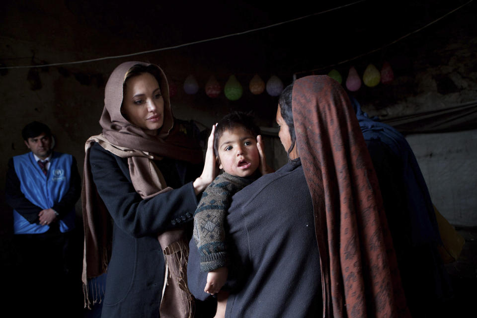 UNHCR Goodwill Ambassador Angelina Jolie (L) meets with  35-year-old Khanum Gul, a mother of eight and her youngest son, Samir at their makeshift home at Tamil Mill Bus site in Kabul in this March 2, 2011 handout photo.   REUTERS/UNHCR/Jason Tanner/Handout (AFGHANISTAN - Tags: POLITICS ENTERTAINMENT) NO COMMERCIAL OR BOOK SALES. FOR EDITORIAL USE ONLY. NOT FOR SALE FOR MARKETING OR ADVERTISING CAMPAIGNS. THIS IMAGE HAS BEEN SUPPLIED BY A THIRD PARTY. IT IS DISTRIBUTED, EXACTLY AS RECEIVED BY REUTERS, AS A SERVICE TO CLIENTS. MANDATORY CREDIT
