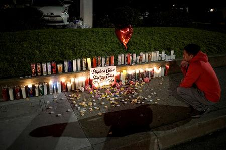 FILE PHOTO: A man pauses at a sidewalk memorial to Stephon Clark, in Sacramento, California, U.S. March 23, 2018.  REUTERS/Bob Strong/File Photo