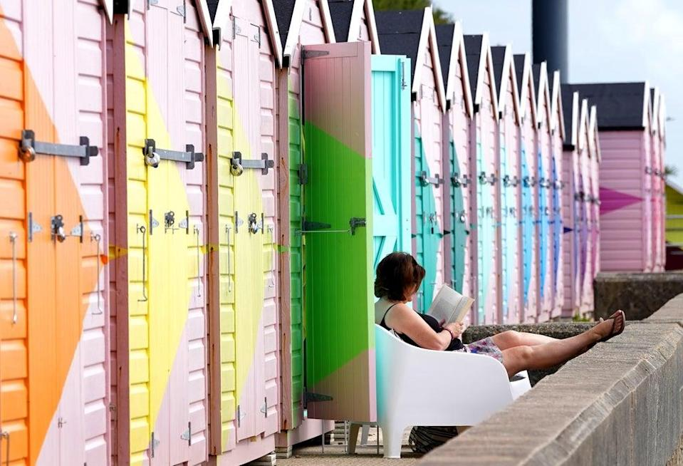 A lady enjoys her newly refurbished beach hut during the fine weather in Folkestone, Kent (Gareth Fuller/PA) (PA Wire)
