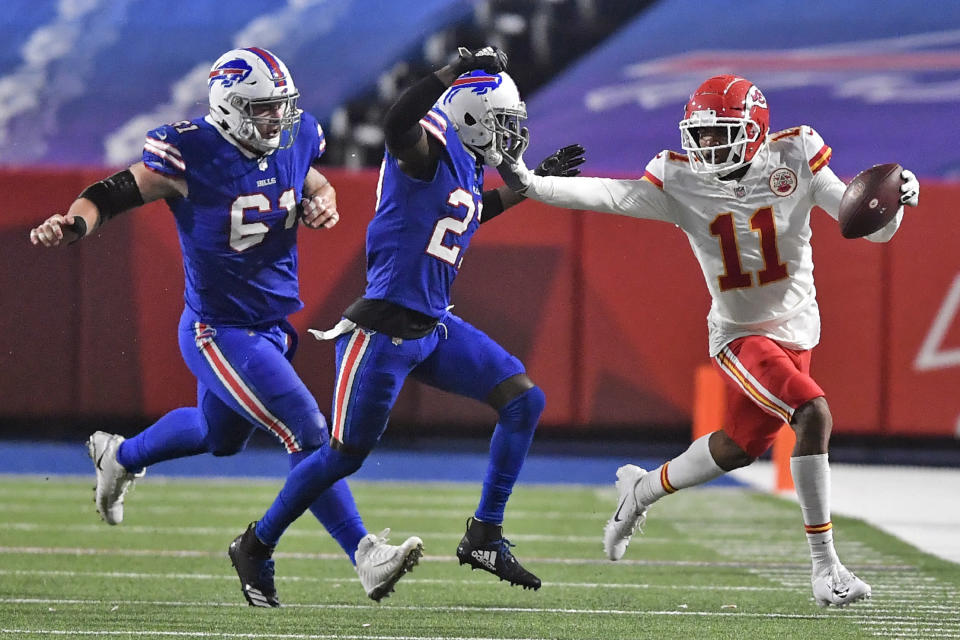 Kansas City Chiefs' Demarcus Robinson (11) holds off Buffalo Bills' Tre'Davious White (27) as Bills' Justin Zimmer (61) also pursues during the second half of an NFL football game, Monday, Oct. 19, 2020, in Orchard Park, N.Y. (AP Photo/Adrian Kraus)