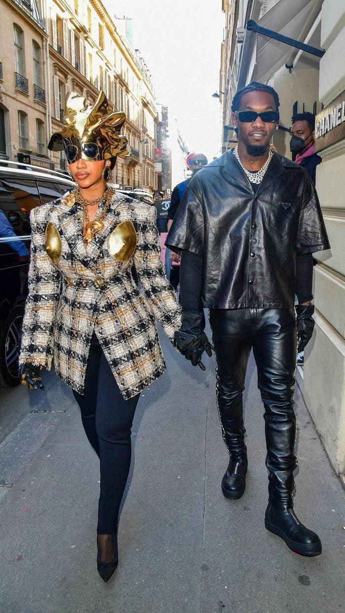Cardi and Offset walking hand in hand on the street, with Cardi wearing a plaid jacket with gold accents and a gold headpiece, and Offset in black leather