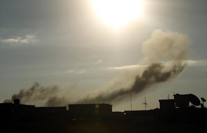 Smoke rises from buildings following an air strike attack early in the morning on August 27, 2014, near military camps in Libya's eastern coastal city of Benghazi (AFP Photo/Abdullah Doma)