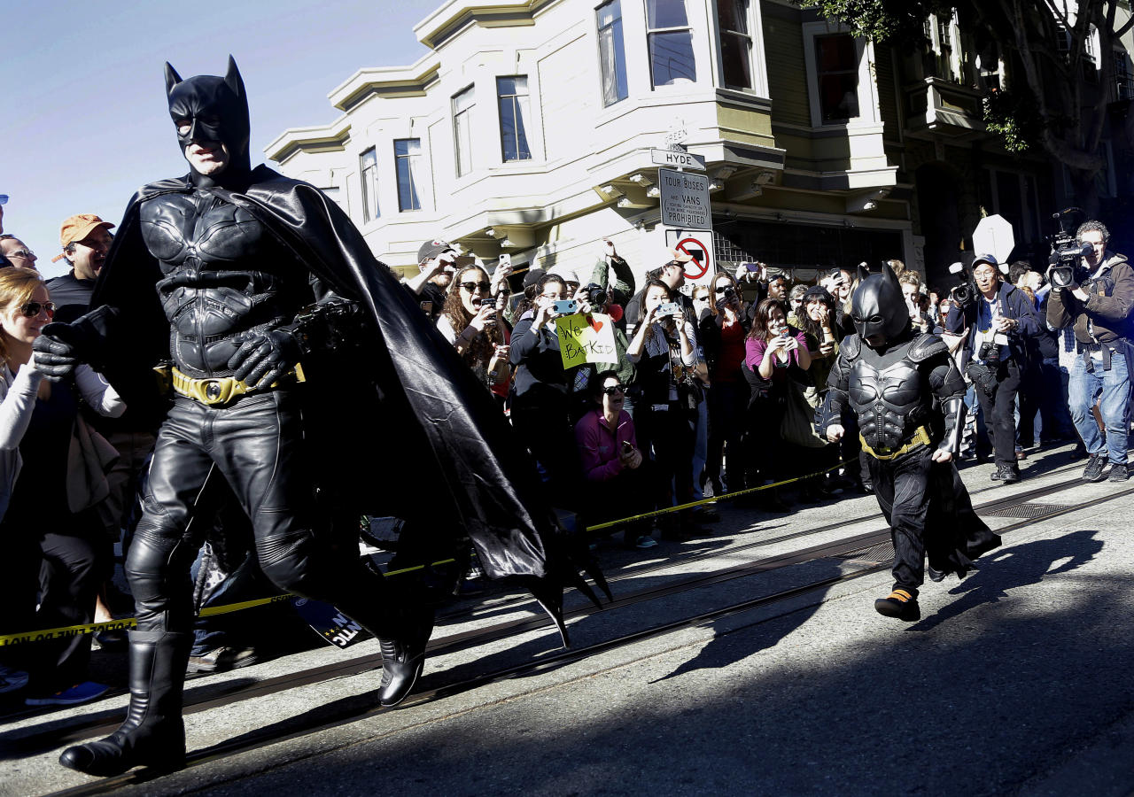 """Miles Scott, dressed as Batkid, right, runs with Batman after saving a damsel in distress in San Francisco, Friday, Nov. 15, 2013. San Francisco turned into Gotham City on Friday, as city officials helped fulfill Scott's wish to be """"Batkid.""""Scott, a leukemia patient from Tulelake in far Northern California, was called into service on Friday morning by San Francisco Police Chief Greg Suhr to help fight crime, The Greater Bay Area Make-A-Wish Foundation says. (AP Photo/Jeff Chiu)"""
