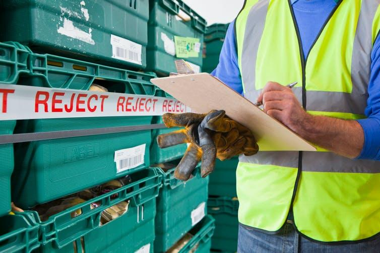 Worker with rejected produce in food processing warehouse.