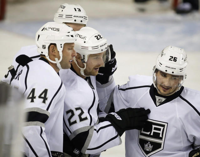 Los Angeles Kings' Trevor Lewis, center, celebrates his goal with teammates during the first period of an NHL hockey game against the Calgary Flames in Calgary, Alberta, Monday, March 10, 2014. (AP Photo/The Canadian Press, Jeff McIntosh)