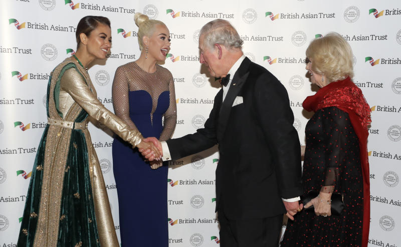 Britain's Prince Charles, Royal Founding Patron of the British Asian Trust, and his wife Camilla, Duchess of Cornwall, meet musician American Katy Perry, second left, and Indian businesswoman Natasha Poonawalla, left, as they arrive to attend a reception for supporters of the British Asian Trust in London, Tuesday, Feb. 4, 2020. (AP Photo/Kirsty Wigglesworth, pool)