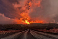 A glowing river of lava gushes from the slopes of Mt Etna, Europe's largest active volcano, near Zafferana Etnea, Sicily, early Wednesday, March 10, 2021. Wednesday's activity is the 11th major eruption in the past few weeks. (AP Photo/Salvatore Allegra)