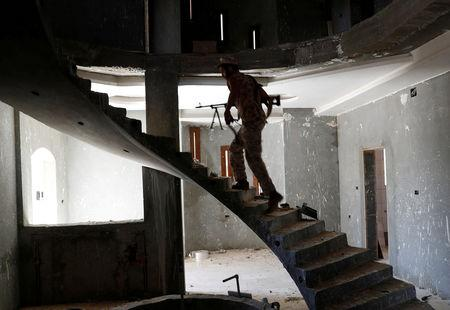 FILE PHOTO: A fighter loyal to Libyan internationally recognised government walks inside a building at outskirts of Tripoli, Libya May 16, 2019. REUTERS/Goran Tomasevic/File Photo